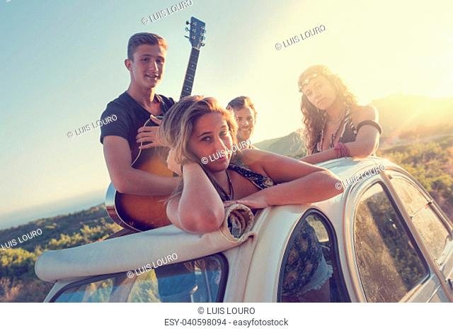 Group of happy people in a car at sunset in summer