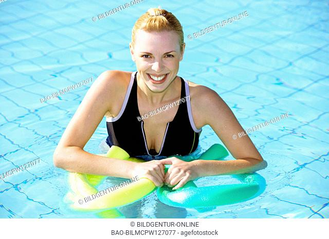 young woman doing aquaaerobic in the swimmingpool
