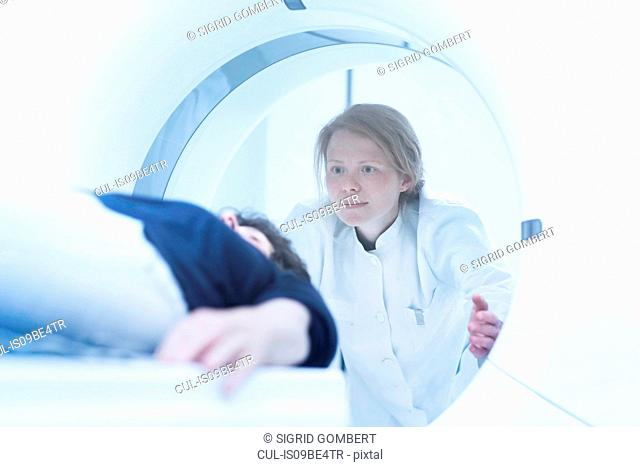 Mature woman having CT scan, radiologist standing beside tunnel