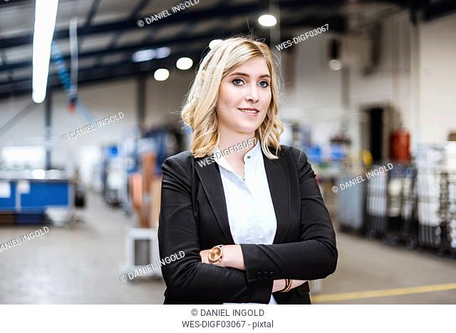 Blonde businesswoman standing on shop floor with arms crossed, portrait