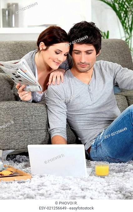 Couple sat on couch with newspaper and laptop