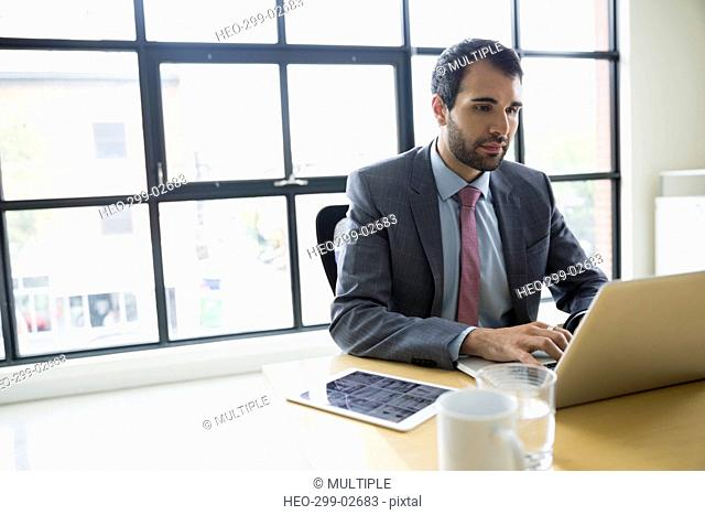 Businessman working at laptop in conference room