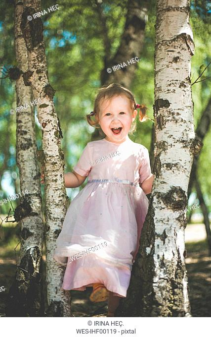 Portrait of happy little girl playing between birch trees