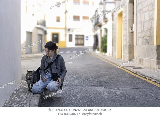 Teenage girl with her photo camera greeting a street cat in the town of Altea, in the province of Alicante, Spain