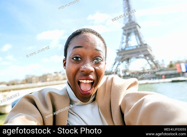 Shocked woman taking selfie with Eiffel Tower in background, Paris, France