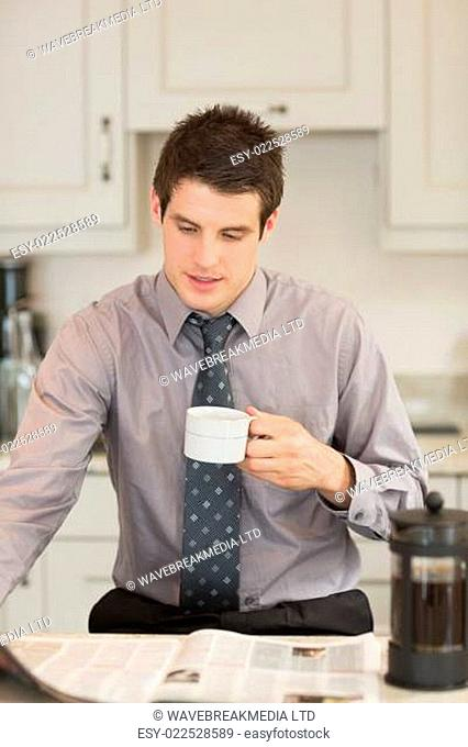 Man turning the page while drinking coffee in kitchen