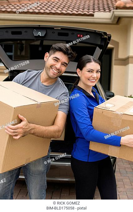 Hispanic couple carrying cardboard boxes near car