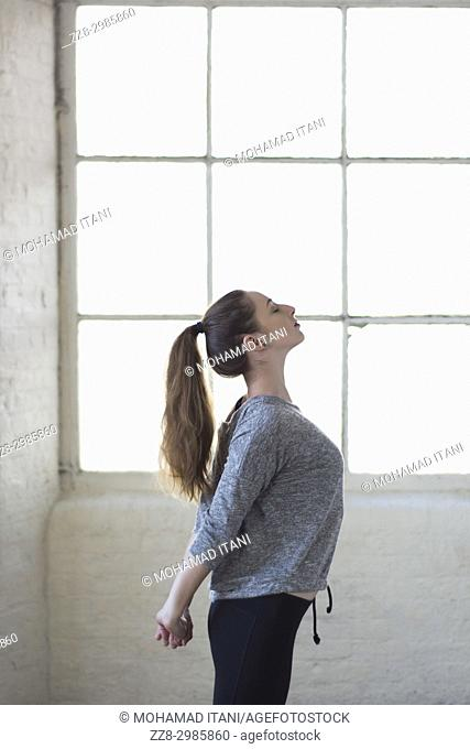 healthy young woman stretching arms by the window