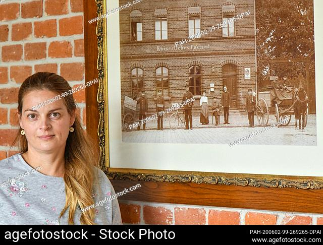 27 May 2020, Brandenburg, Biesenthal: Pamela John, operator of the Imperial Post Office, is standing next to a historical photo of the Imperial Post Office from...