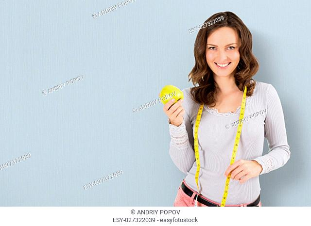 Portrait Of A Young Woman With Measuring Tape And Green Apple On Colored Background