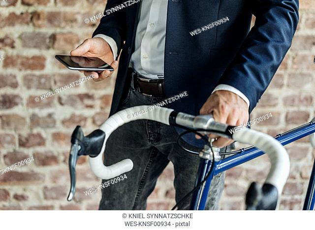 Close-up of businessman with bicycle checking cell phone