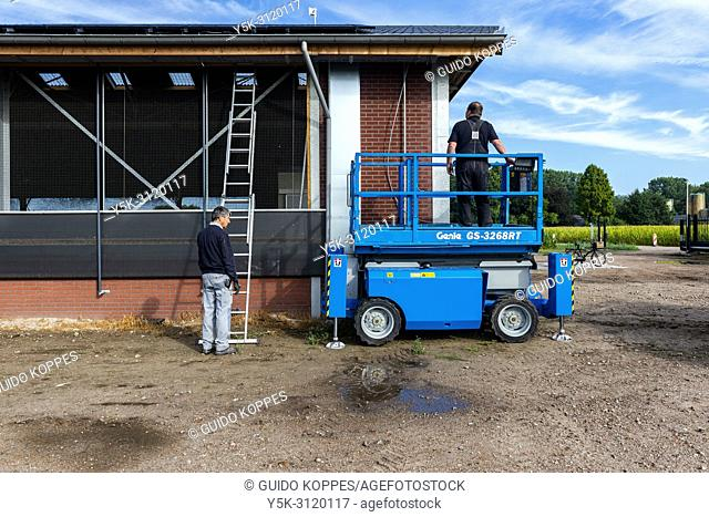 Goirle / Hilvarenbeek, Netherlands. Two Electrician craftsmen installing Solar Cell Panels on the roof of a agricultural bull meat farm