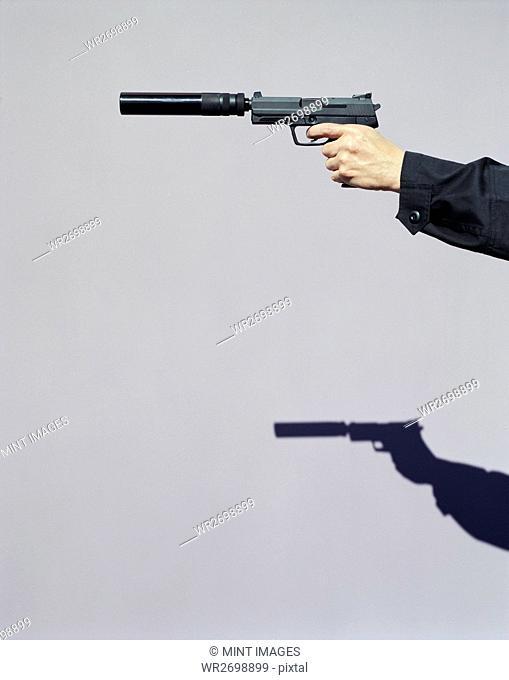 Detail of man aiming high powered hand gun with silencer