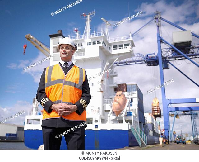 Portrait of ship's captain standing in front of container ship