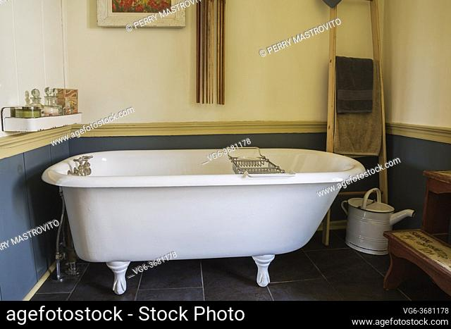 White claw foot bathtub in main bathroom with black ceramic tile floor inside an old 1841 cottage style fieldstone house, Quebec, Canada