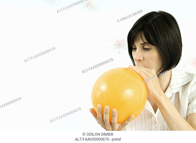 Woman inflating balloon