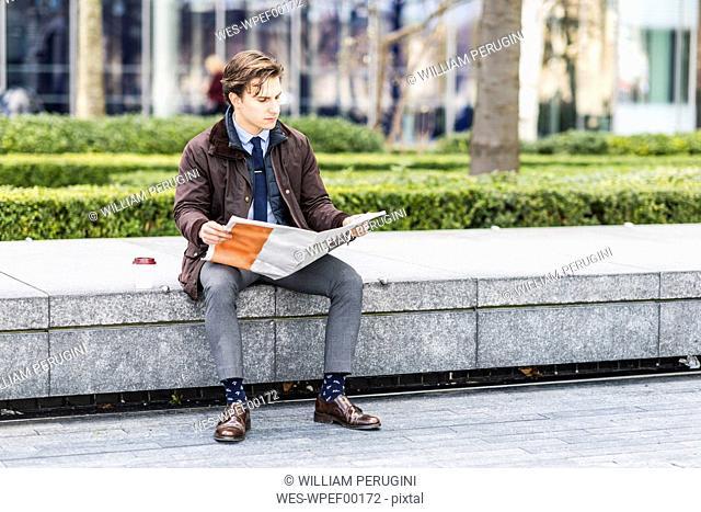 Businessman reading newspaper outdoors