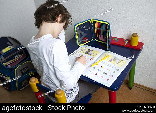 """Erstklaessler (7 years) sits at a table at home and does German tasks in his booklet """"""""Alphabet booklet - basic font"""""""", on May 4th"""