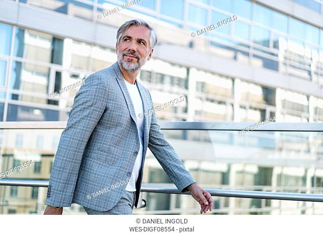 Confident mature businessman on the go looking around