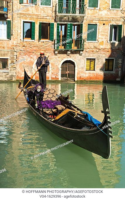 A masked woman during carnival in a gondola, Venice, Italy, Europe