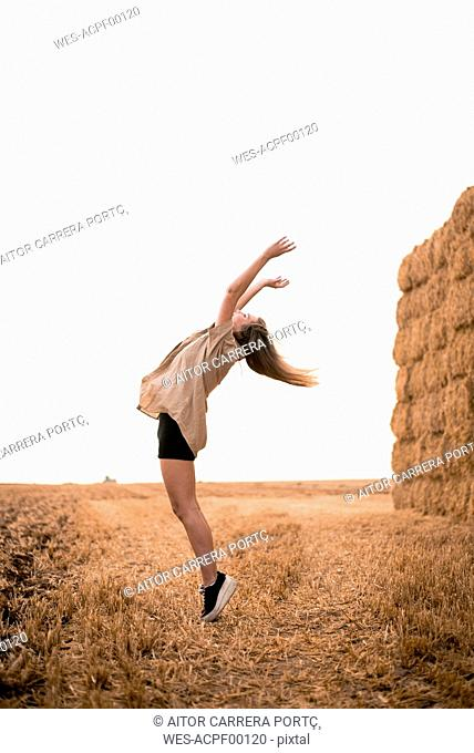 Happy young woman jumping in field