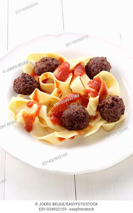 fettuccine with tomato sauce and meat balls on a white plate