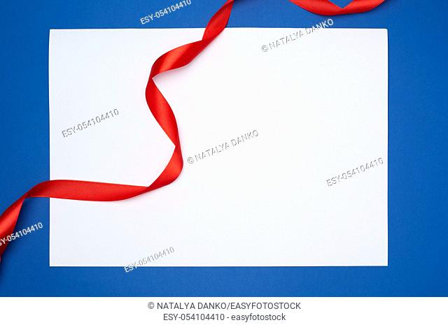 empty white sheet of paper and red silk twisted ribbon on a blue background, place for test, holiday backdrop