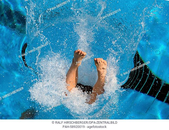 A swimming supervisor at the Kiebitzberge swim club dives into the outdoor pool, which registers a water temperature of around 20 degrees celsius