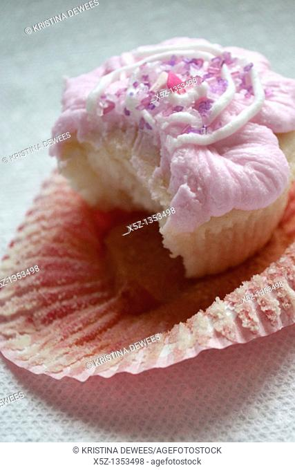 A pink frosted cupcake missing one bite