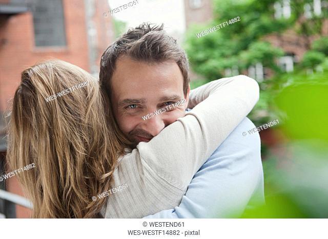 Germany, Couple hugging at balcony, man smiling