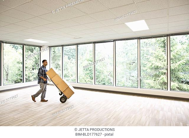 Mixed race businessman wheeling boxes in empty office