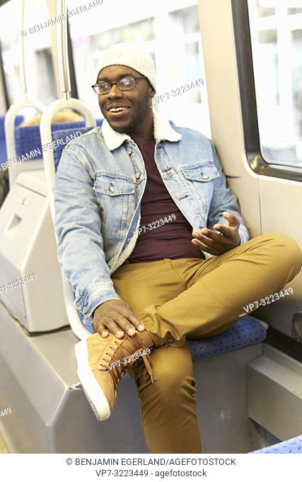 man sitting in streetcar, tram, public transport, in Munich, Germany