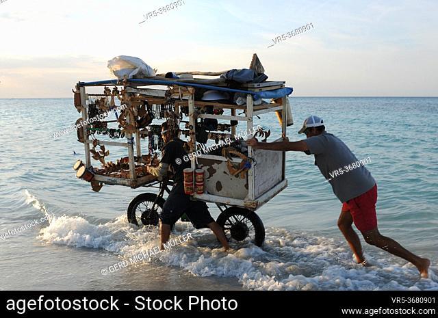 Cuba: Beach souvenier trader at Varadero beach pushing his heavy biciycle through the ocean