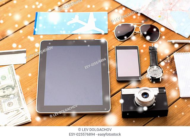 travel, tourism, winter holidays and technology concept - smartphone with tablet pc computer, airplane ticket and personal stuff over snow