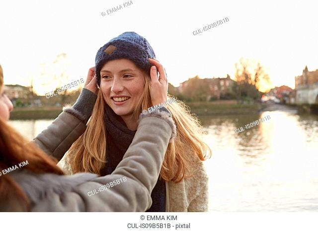 Young woman putting knitted hat on friend, outdoors, smiling