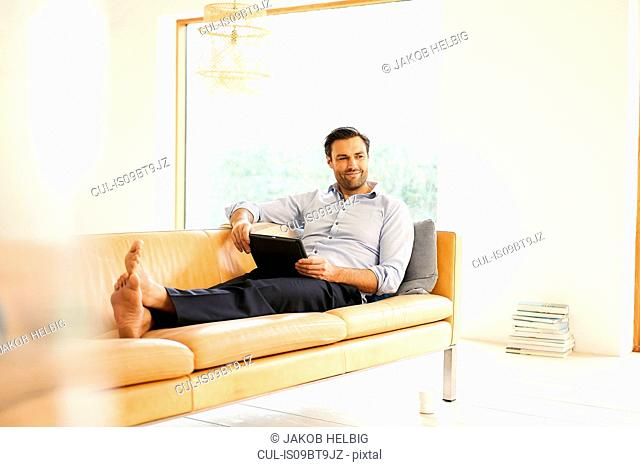 Mature man with digital tablet reclining on sofa