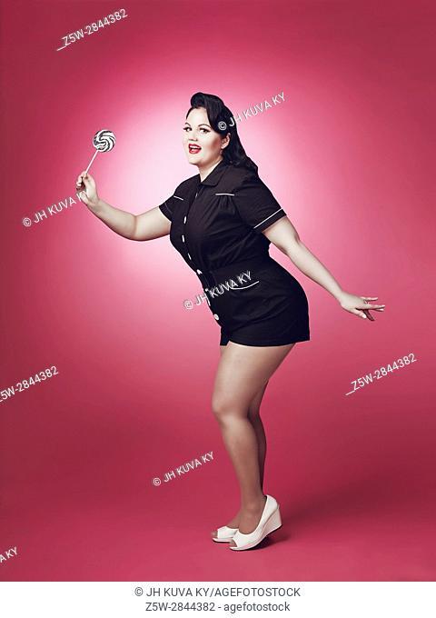 Beautiful woman wearing black shorts suit, pin-up theme, pink background