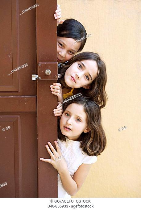 Girls peeking from behind door