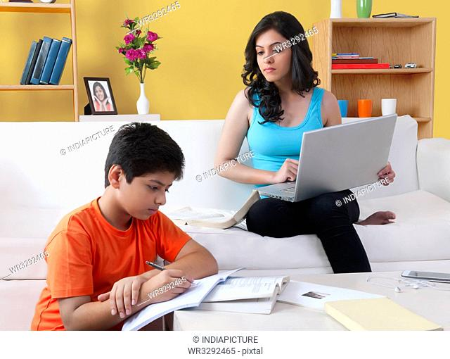 Brother doing homework while his sister using laptop