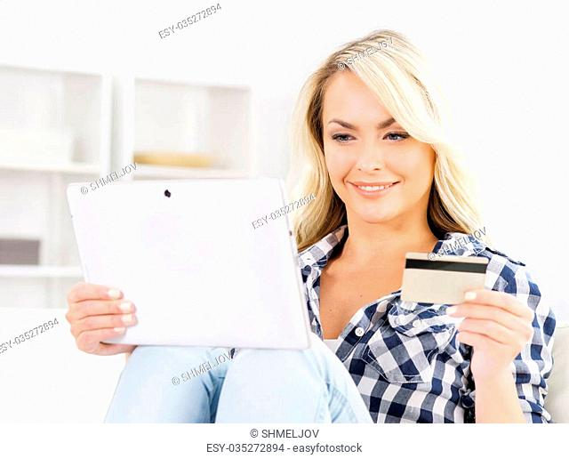 Attractive blond woman with a credit card and a tablet computer