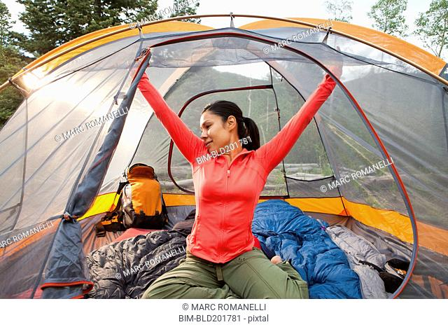 Mixed race woman stretching in tent