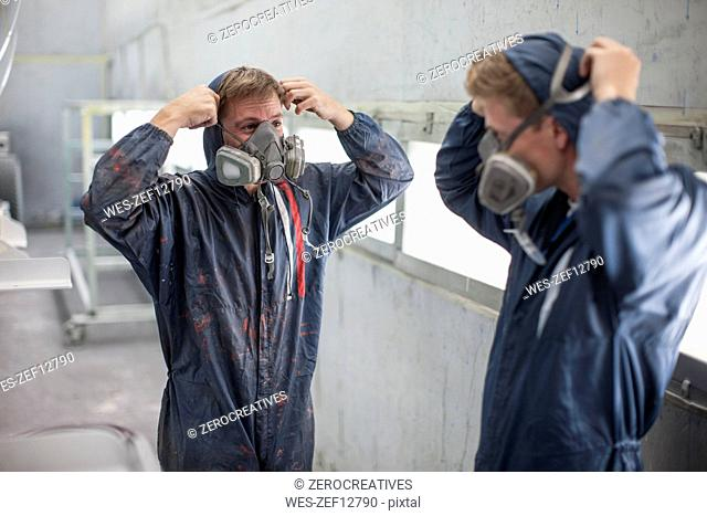 Factory worker in truck manufacture adjusting respirators