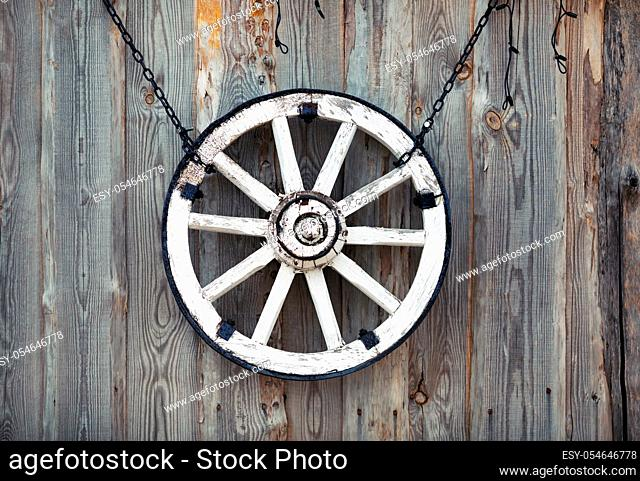 Old cart wheel hanging on vintage wooden wall