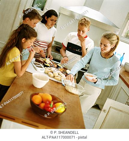 Young people snacking around table in kitchen