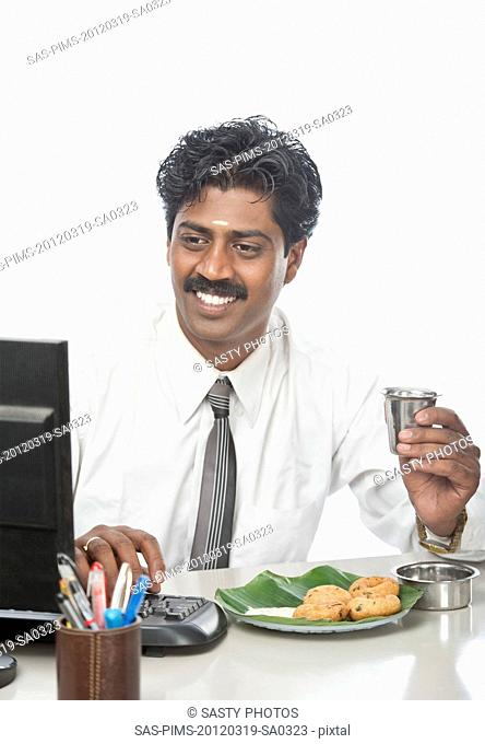 South Indian businessman working in an office and having food