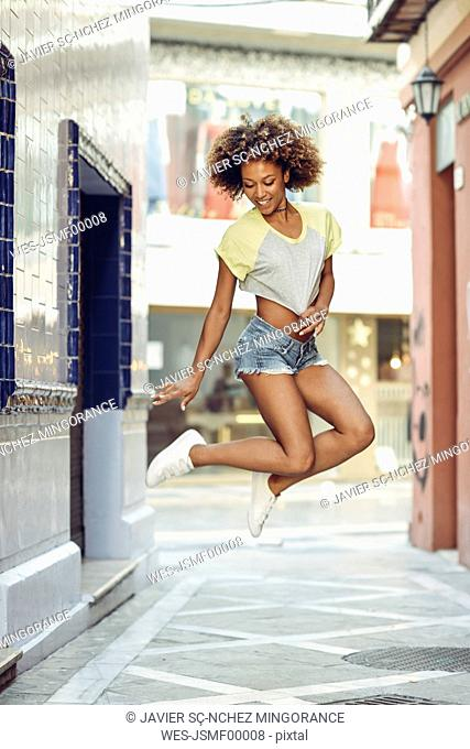 Happy woman with afro hairstyle jumping in a lane