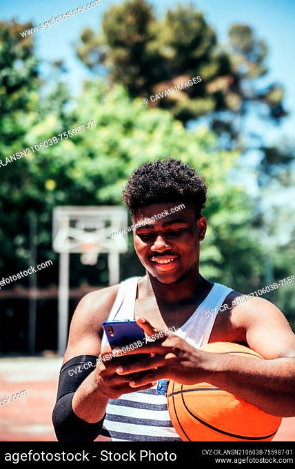 Portrait of a black African-American boy using his mobile phone on an urban basketball court