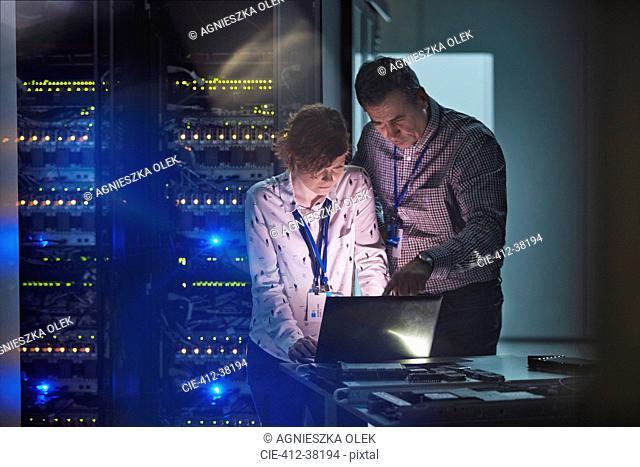 IT technicians working at laptop in dark server room