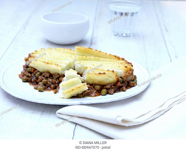 Still life of cottage pie with minced beef, gravy and vegetables on white plate