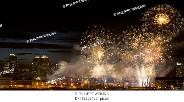 Fireworks in front of modern city skyline; Calgary, Alberta, Canada